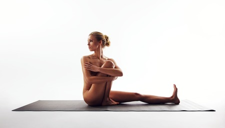 Yoga pose demonstrated by beautiful woman. Nude woman sitting on exercise mat performing yoga over white background. photo