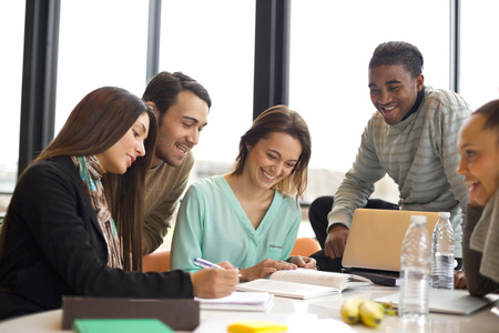 Group of multiracial young students studying together at a table. Mixed race people doing group study. photo