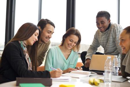 multiracial 젊은 학생들의 그룹 테이블에서 함께 공부. 그룹 연구를하고 혼합 된 경주 사람들. 스톡 콘텐츠