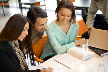 Group of students studying in a library. Young people sitting together at table working on school assignment. photo