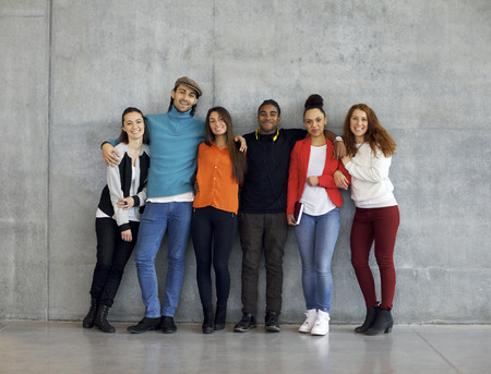 standing against: Multiethnic group of happy young university students on campus. Mixed race young people standing together against wall in college. Stock Photo