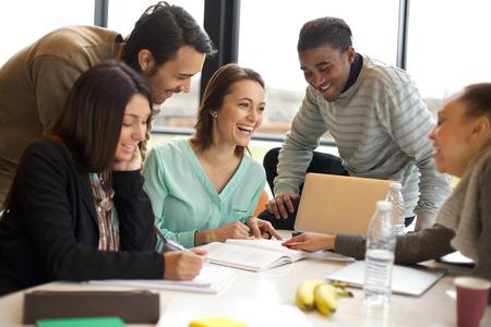 テーブルでのグループ学習を楽しんでいる多民族の若者。幸せな大学の学生は彼らのプロジェクトの情報を研究するため本やノート パソコンのテー