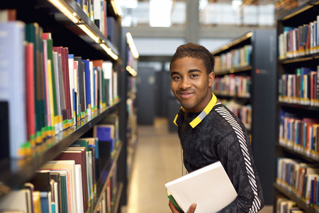 public library: Image of happy young man standing by book shelf in library. African american student in public library holding books for reference studies.