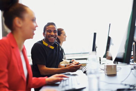computer training: Young afro american man looking at camera smiling while working on computer in modern classroom. Young students sitting at college computer lab. Stock Photo