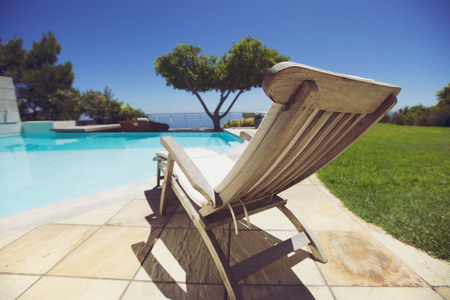 Long deck chair by the swimming pool. Empty wooden lounge chair next to pool at holiday resort. photo