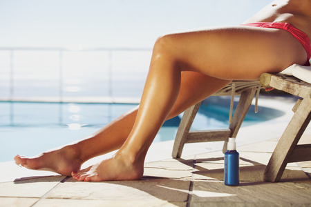 Young female relaxing on lounge chair with a suntan spray by the pool. Young lady sunbathing by the swimming pool. photo