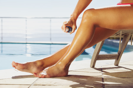 recliner: Woman applying suntan spray onto her legs. Female sitting on recliner chair by the swimming pool sunbathing.