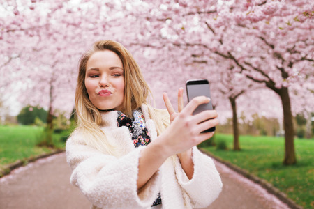 Cute young woman gesturing peace sign while taking her picture with mobile phone. Caucasian female model at spring blossom park taking self portrait with smart phone. photo