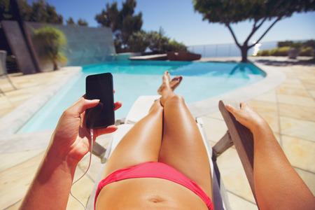 プールでスマート フォンを保持している若い女性。女性モデル携帯電話を用いたデッキチェアでリラックス。 写真素材
