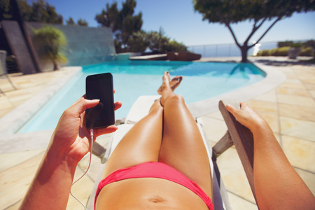 sunbathing: Young woman holding a smart phone by the pool. Female model relaxing on a deckchair using mobile phone. Stock Photo