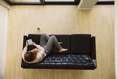 Top view of young lady sitting on a couch using digital tablet. Female relaxing on sofa with a e-reader in her apartment.