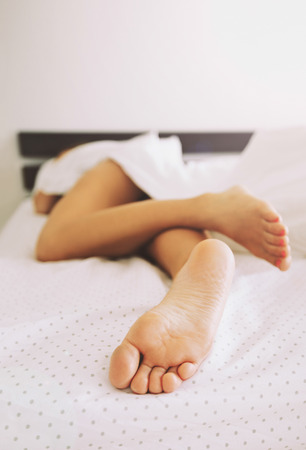 Bare legs of a young woman sleeping in her bed at home. Focus on legs.