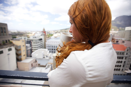 over the shoulder view: Attractive brunette standing on a balcony holding a cup of coffee. Young woman looking out from a balcony while drinking coffee.