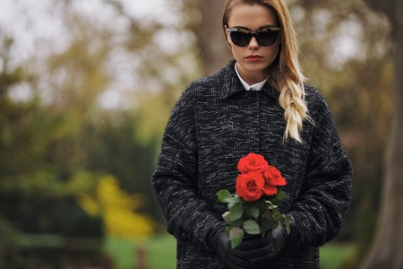 Portrait of young woman in black dress at graveyard holding fresh flowers. Caucasian female at cemetery with red roses.