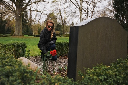 grieving: Woman with flowers crouching at cemetery