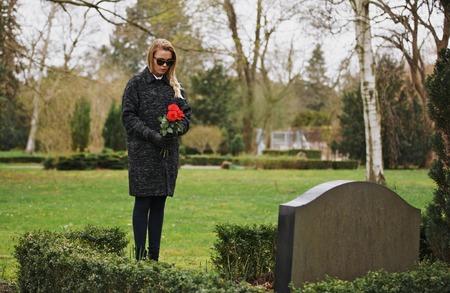 Jonge vrouw een bezoek aan een geliefde op de begraafplaats te betalen opzichten met verse roze bloemen. Vrouw rouwt op kerkhof.