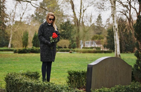 grieving: Young woman visiting a loved one at the cemetery paying respects with fresh rose flowers. Female grieving at graveyard.