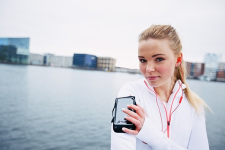 Female athlete training outdoors, using a smartphone to monitor her progress. Fit and sporty young female athlete wearing arm band. photo