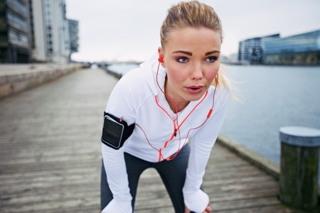 taking a break: Young woman taking a break from exercise outdoors. Fit young female athlete stopping for rest while jogging along the river.