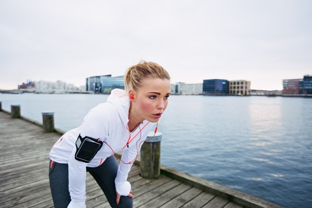 taking a break: Female runner standing bent over and catching her breath after a running session along river. Young woman taking break after a run.