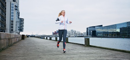 Young female athlete running on boardwalk along the river. Fit young woman jogging along the waterfront. photo