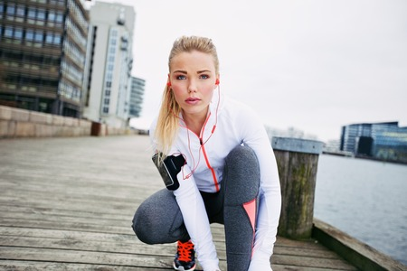Fitness woman on boardwalk crouching to tie her shoelace looking at camera. Confident young female jogger training outdoors. photo