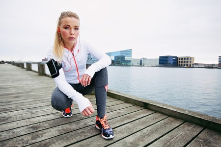 taking a break: Young woman runner resting after running workout. Female fitness model crouching on sidewalk along river. Female jogger taking a break. Stock Photo