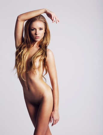 Portrait of gorgeous young nude woman posing against grey background. Sexy caucasian female model. Stock Photo