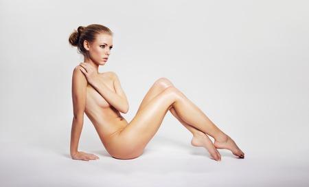 mujer desnuda sentada: Mujer desnuda sensual sentada en el suelo que cubre su pecho con la mano y mirando a otro lado en copyspace. Mujer desnuda bastante joven sentado sobre fondo gris.