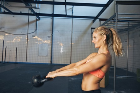 Side view of happy young  woman exercising with kettle bell at gym. Caucasian female athlete doing crossfit workout at gym. photo