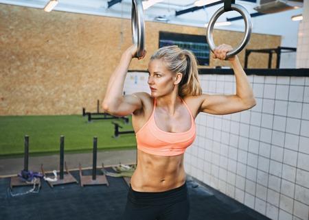 gymnastik: Fit junge Frau mit Turner-Ringe in der Turnhalle entfernt suchen. Junge kaukasische Frau, die Aus�bung im Fitnessstudio.