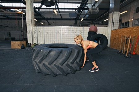 Tough female athlete flipping a huge tire. Young woman doing crossfit exercise at gym. photo