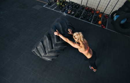 Crossfit woman exercising at gym. Muscular female flipping huge tire photo