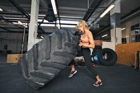 체육관에서 타이어를 내리고 근육 젊은 여자. 크로스 핏 체육관에서 타이어 플립을 수행 맞는 여성 선수.