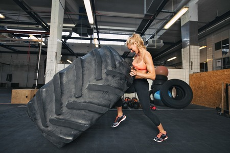 Muscular young woman flipping tire at gym. Fit female athlete performing a tire flip at crossfit gym. Stock Photo