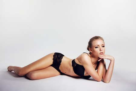 Sensual young woman in lingerie lying over grey background. Pretty young caucasian female model wearing black underwear looking away. Woman posing in lingerie photo