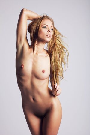 Portrait of nude young woman posing against grey background. Sensual young woman holding her hair while posing naked.
