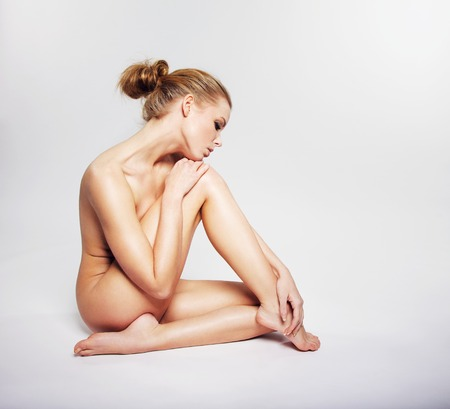 naked woman sitting: Pensive naked woman sitting on grey background. Caucasian woman sitting nude with her leg covering her body Stock Photo