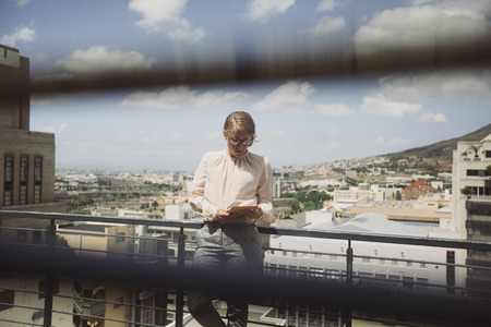 balcony window: Image through window blinds of a young woman using digital tablet on a balcony with view of city