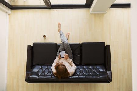 cenital: Vista superior de la se�ora joven relajado sentado en un sof� que trabaja en una tableta digital. Vista a�rea de la mujer sentada en el sof� con tablet PC.
