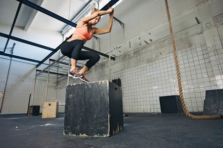 크로스 핏 스타일의 체육관에서 점프하는 젊은 여자 상자를 맞 춥니 다. 여성 운동 선수는 상자 체육관에서 점프를 수행하고 있습니다. 스톡 콘텐츠