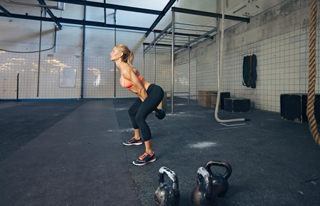 bells: Young fitness female exercise with kettle bell. Caucasian woman doing crossfit workout at gym. Stock Photo