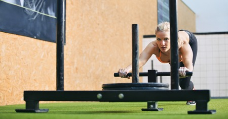 Fêmea jovem musculoso e forte empurrando o equipamento de exercício gatuno em relva artificial. Mulher apta que exercita na academia crossfit. Imagens