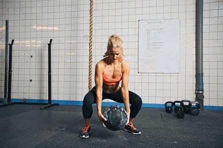 Fit und stark Sportlerin arbeitet mit einem Medizinball, um eine bessere Kernstärke und Stabilität zu erhalten. Frau macht Crossfit Workout im Fitnessstudio.