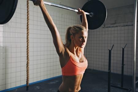 強い女性が crossfit 運動ルーチンの一部としてバーベルを持ち上げます。フィット若い女性ジムで重い重量を持ち上げます。