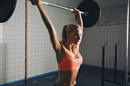 Strong woman lifting barbell as a part of crossfit exercise routine. Fit young woman lifting heavy weights at gym.