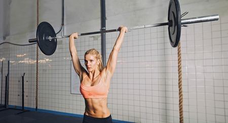 levantar pesas: Mujer joven muscular que hace levantamiento de pesas en el gimnasio de crossfit. Modelo femenino Fit levantamiento de pesos pesados ??en el gimnasio. Foto de archivo