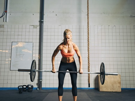 Fit and attractive caucasian female holding a barbell in her hands. Crossfit woman lifting heavy weights in gym.