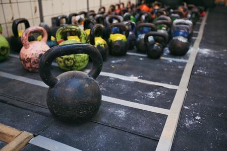 Verschillende maten van de kettlebells gewichten liggen op de sportschool vloer. Apparatuur gebruikt voor CrossFit training bij fitnessclub Stockfoto