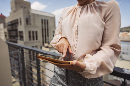 shallow focus: Young woman standing on balcony using tablet PC. Cropped image of female working on digital tablet. Stock Photo